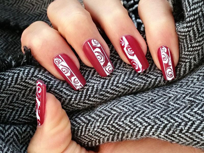 nail art elegante bordeaux su cui sara colleoni ha dipinto rose stilizzate in bianco