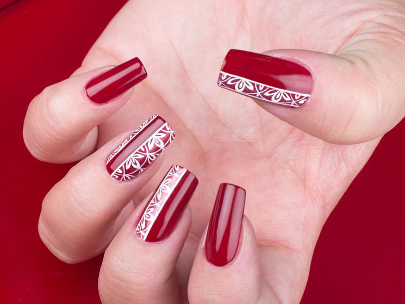 nail art gioia del zotto ha reato una styline con un decoro in bianco effetto pizzo che risalta bellissimo sullo sfondo rosso